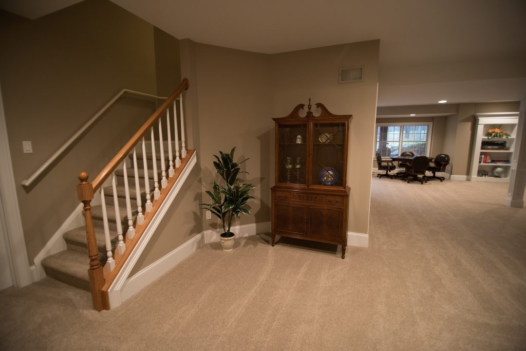 basement staircase with carpet and wood railing